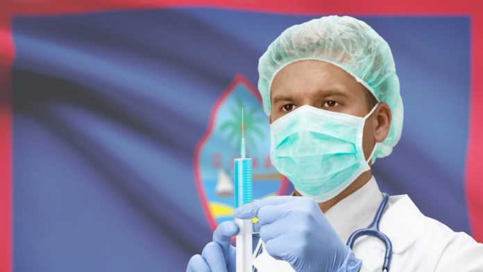 Doctor holding a syringe in front of Guam flag